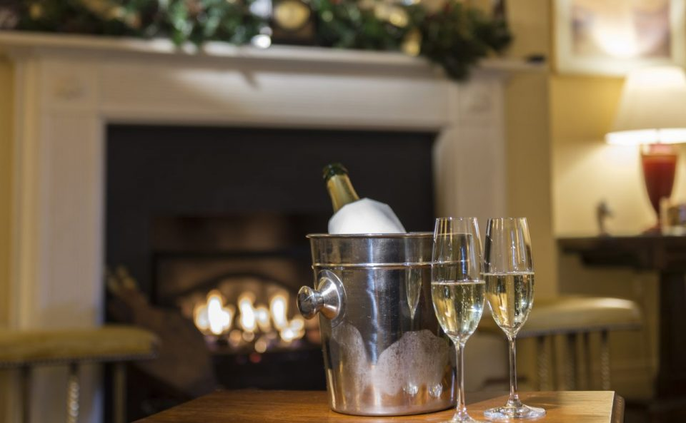 A bottle of fizz in an ice bucket by a festive fire place.